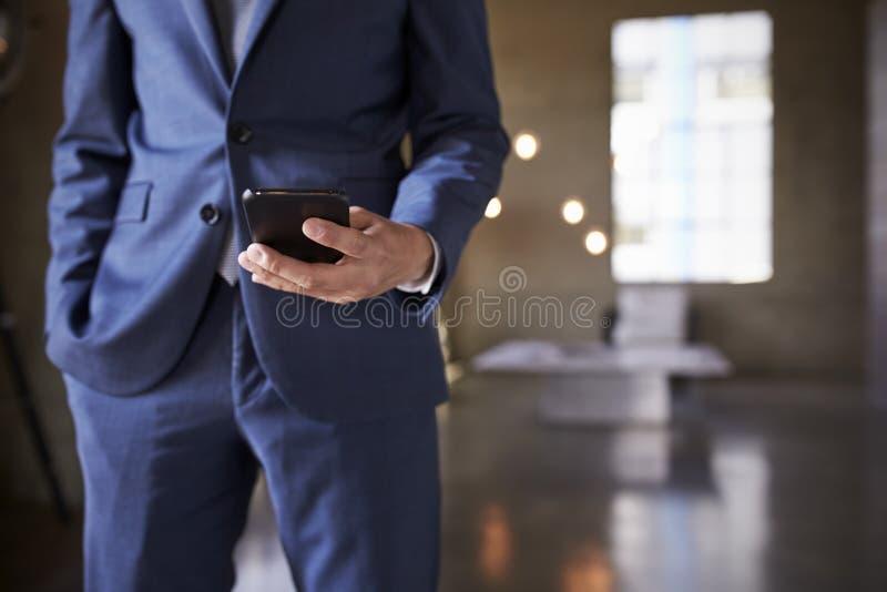 人的中间部分蓝色衣服的使用智能手机,关闭 库存图片