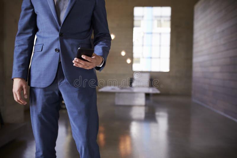 人的中间部分蓝色衣服的使用智能手机 库存图片