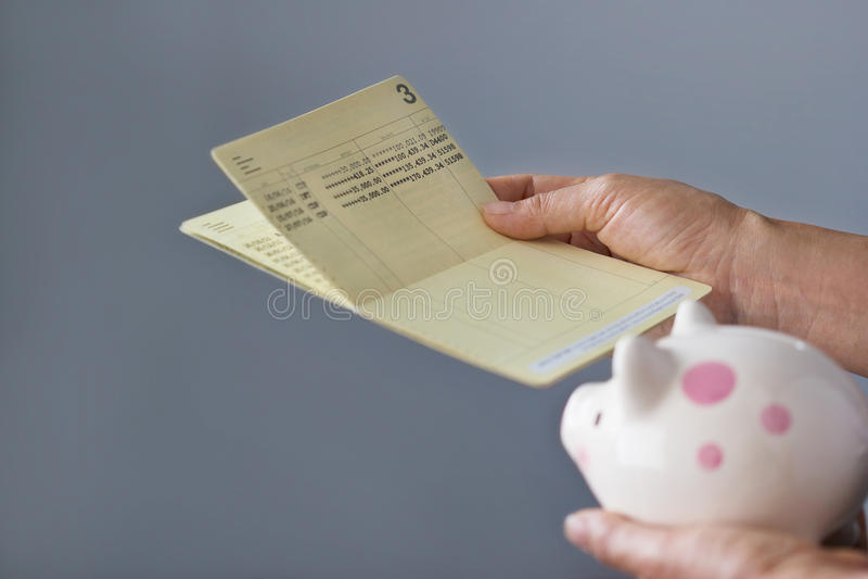 人的举行的储蓄存款存款簿和存钱罐在手上 库存图片