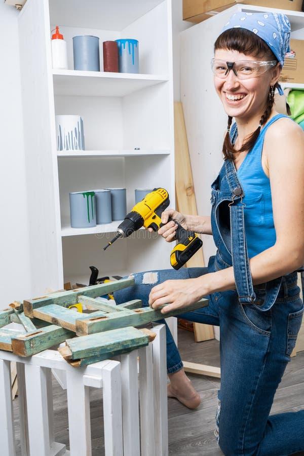 人的事务的妇女:一个女孩一套蓝色牛仔布衣服的和有一把黄色螺丝刀的恢复老凳子 免版税图库摄影