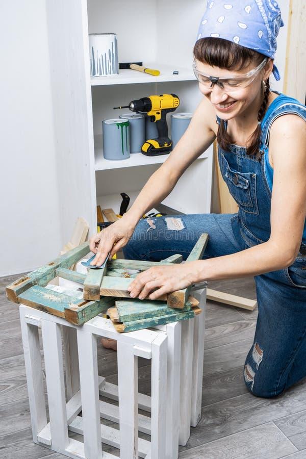 人的事务的妇女:女孩木匠清洗砂纸与一老karsk从家具 恢复椅子 免版税库存图片