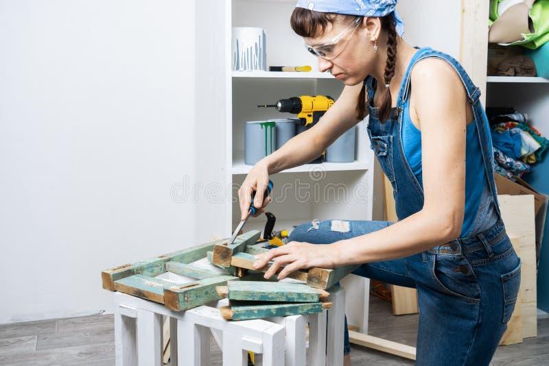 人的事务的妇女:女孩木匠猛击与凿子的一个孔 恢复椅子 免版税图库摄影