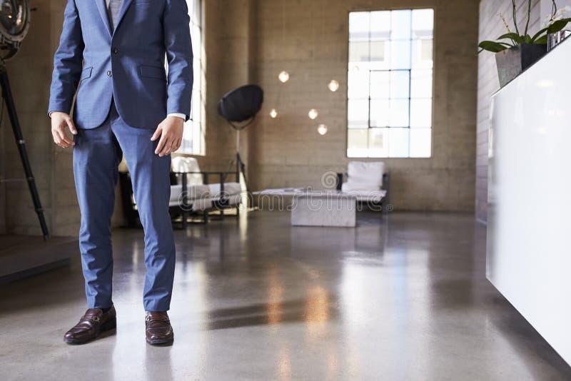 人的低部分站立在现代用装备的室的衣服的 免版税库存照片