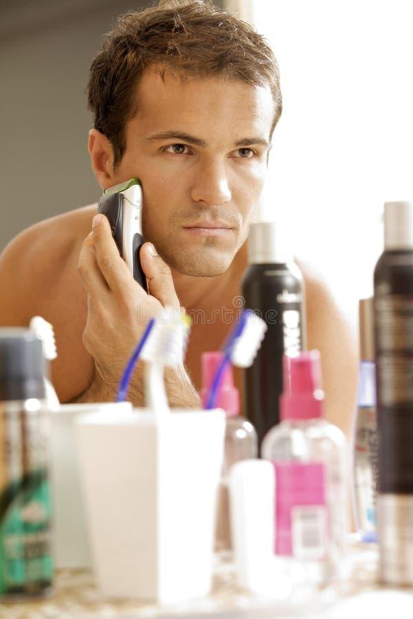 年轻人的反射刮与电动剃须刀的镜子的 库存图片