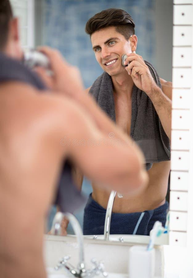 人的反射刮与电动剃须刀的镜子的 库存图片