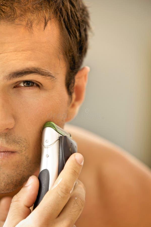 年轻人的反射刮与电动剃须刀的镜子的 免版税库存照片