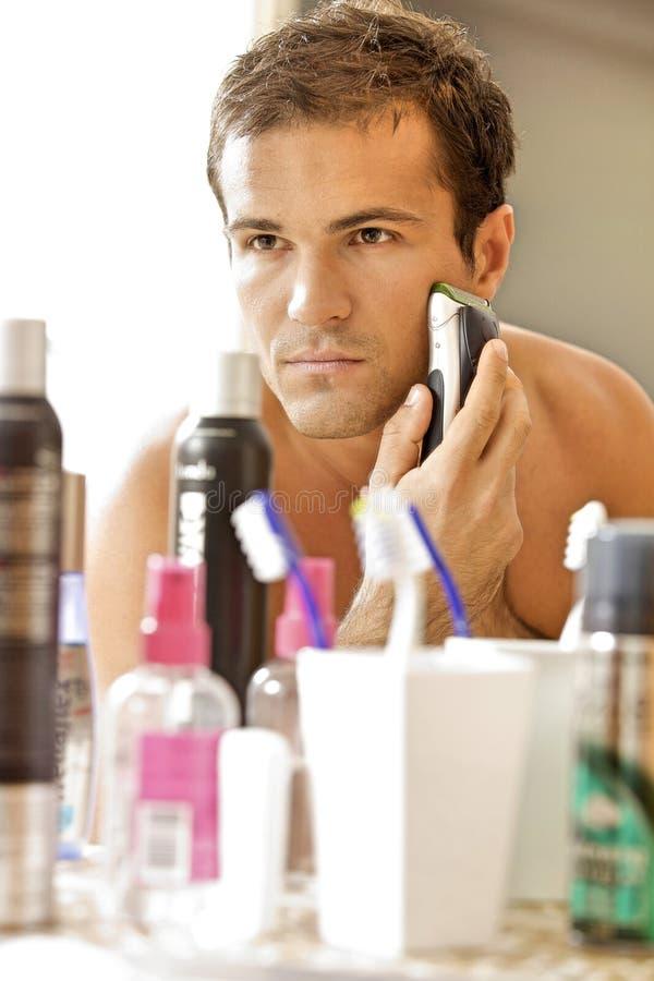 年轻人的反射刮与电动剃须刀的镜子的 免版税库存图片