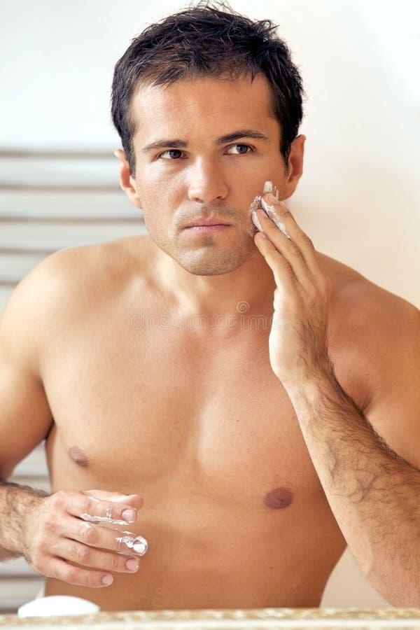 年轻人的反映应用剃须膏的镜子的 免版税库存照片