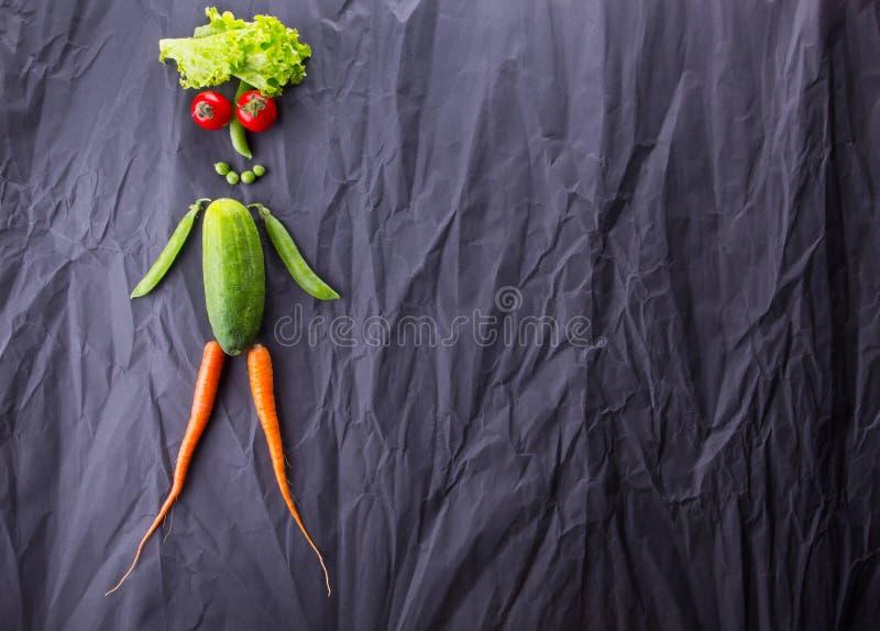 人的图由菜做成在黑纸背景 减肥和健康生活方式 文本的空间 免版税库存图片