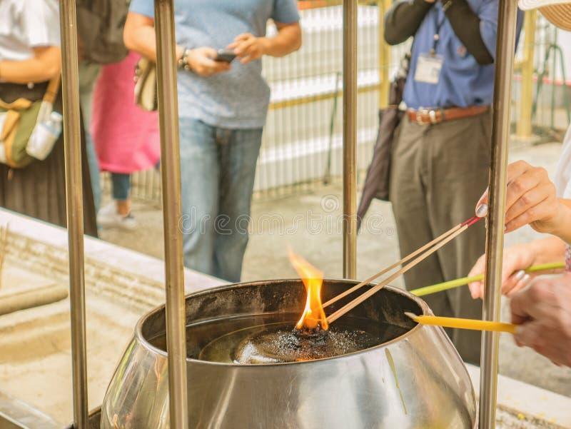 人的在寺庙的手燃烧的香 免版税库存照片