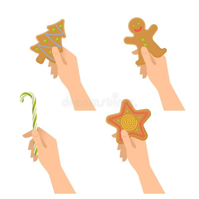 人的手举行圣诞节甜标志:被烘烤的曲奇饼,糖果c 皇族释放例证