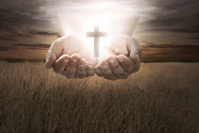 人的手举行基督徒十字架 免版税库存照片