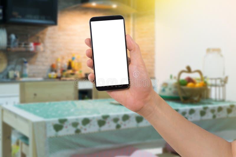 人的手举行巧妙的电话,片剂,有白色黑屏的手机在模糊的厨房室背景 库存照片