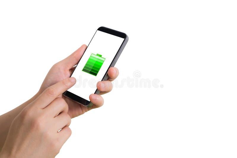 人的手举行智能手机,片剂,有真正充分的电池状态象的手机在屏幕上 库存照片