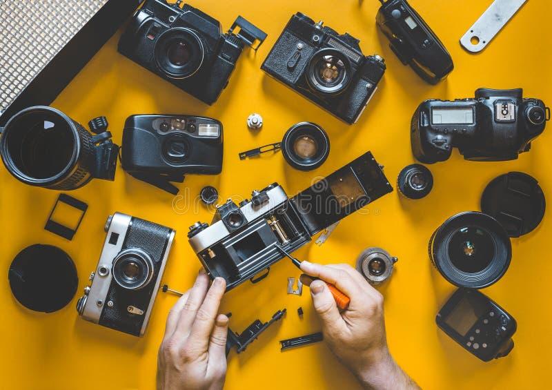 人的手修理打破的影片照相机,顶视图 免版税库存照片