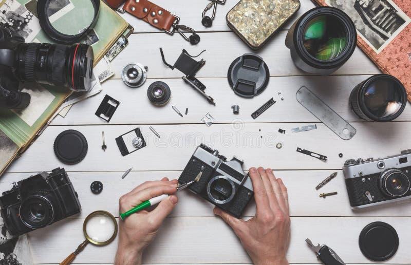 人的手修理照相设备概念残破的影片照相机修理和维护  免版税库存照片