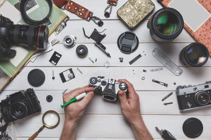 人的手修理照相设备概念残破的影片照相机修理和维护  免版税图库摄影