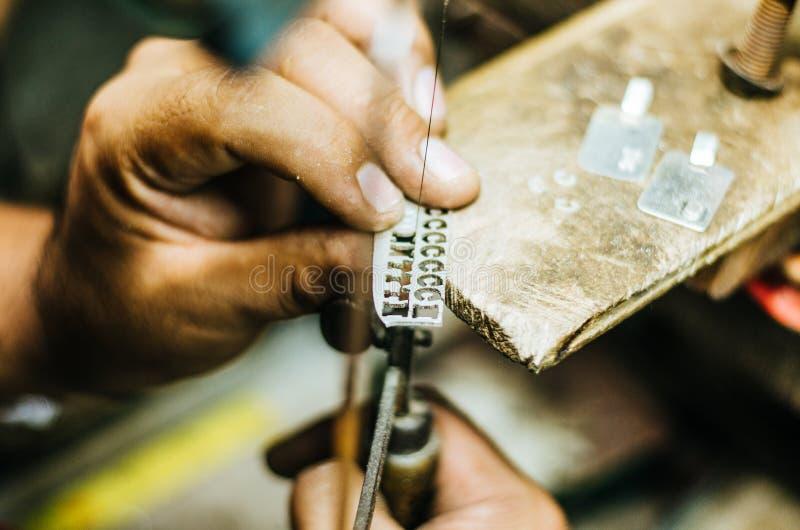 人的手在一个银币的冶金匠工作与金属的在工作表,关闭上看见了,选择的焦点 库存照片