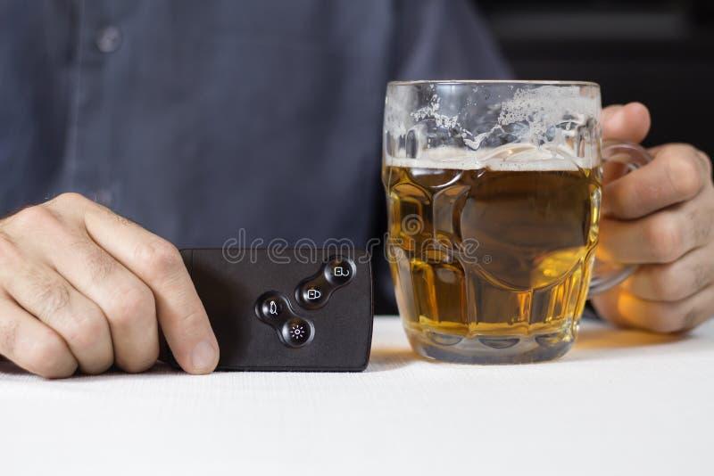 人的手在一只手上拿着在汽车的钥匙卡片,在第二个杯子用啤酒 免版税库存照片
