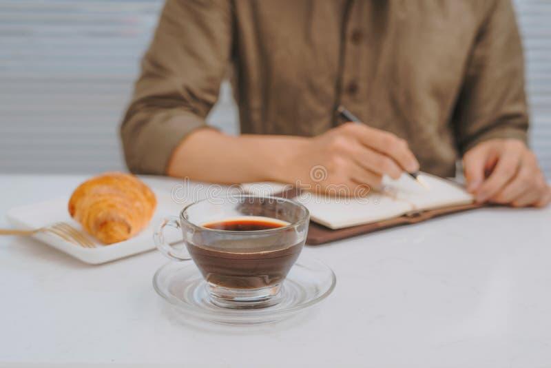 人的手在有笔的白色在木桌,企业葡萄酒概念上的笔记本和新月形面包写了消息 库存图片