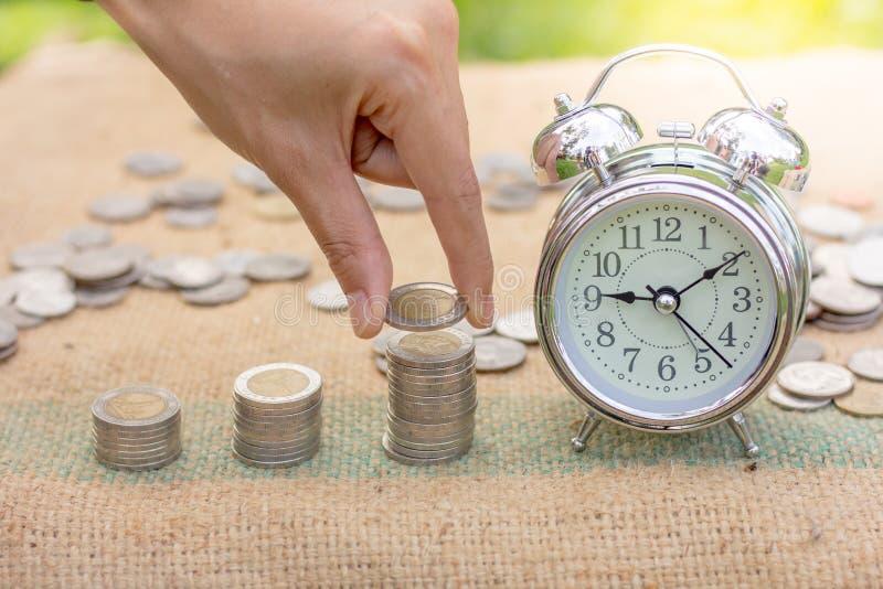 人的手投入硬币对与时钟, Sav的生长硬币堆 免版税库存图片