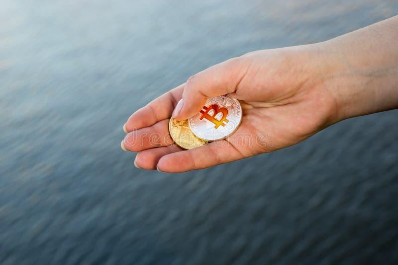 人的手投掷的bitcoins到河里 库存照片