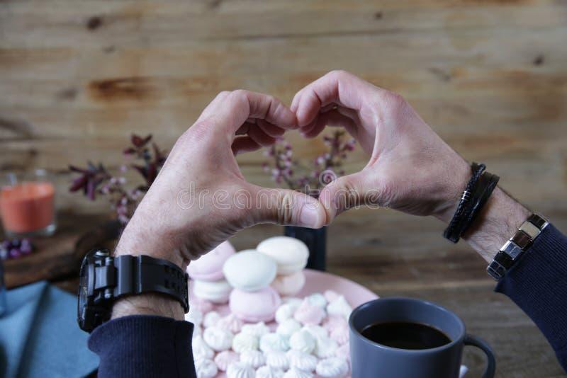 人的手折叠了以心脏以桃红色蛋白软糖为背景,一杯的咖啡的形式 图库摄影