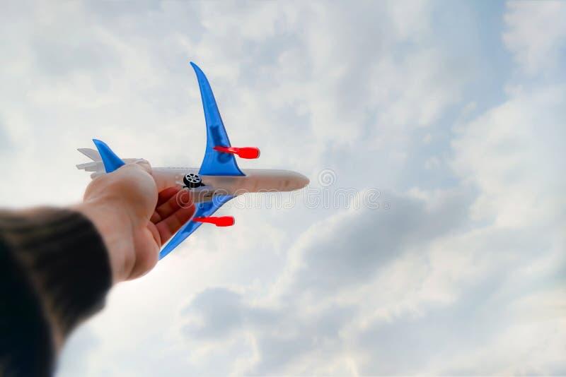 人的手拿着玩具飞机反对天空蔚蓝和白色云彩 自由、飞行和旅行的概念 库存照片