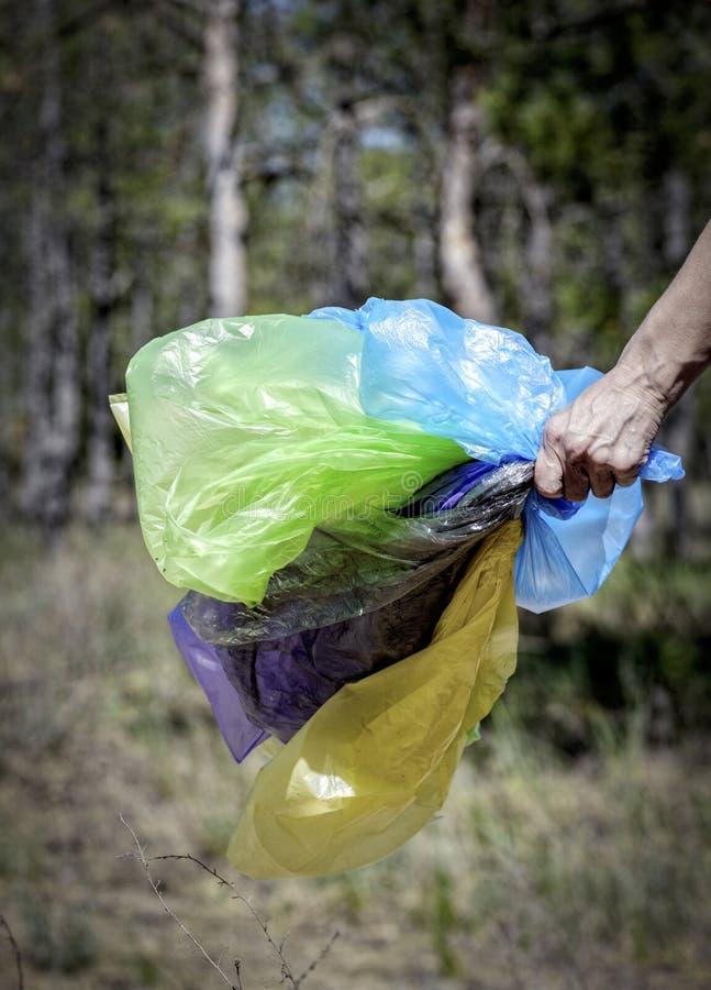 人的手拿着g的许多多彩多姿的空的透明袋子 免版税库存图片