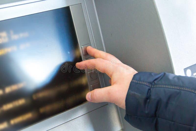 人的手按在现钞机的键盘的按钮 库存照片