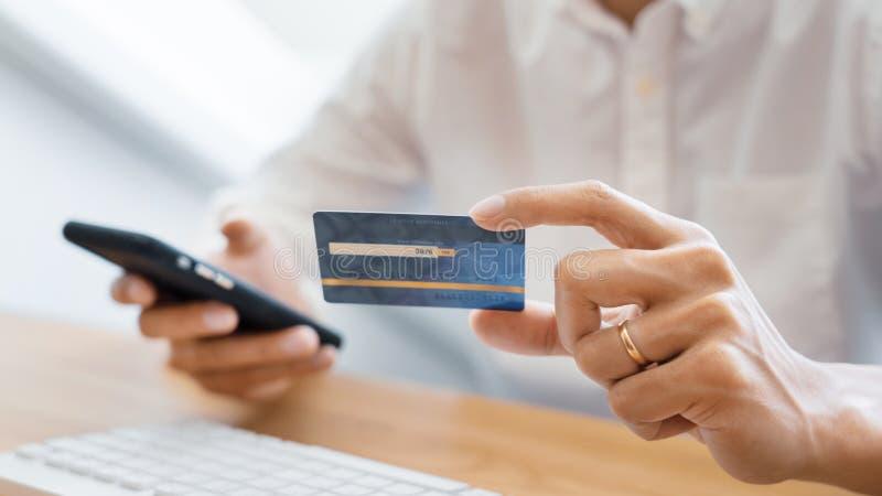 人的手支付与信用卡和使用智能手机的偶然衬衣的为做命令的网络购物通过互联网使用 免版税图库摄影