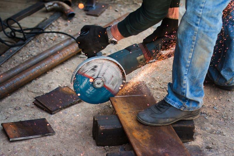 人的手有钢切削刀工具的 工作者外面,切开金属板料  电看了引起热的火花 免版税库存图片