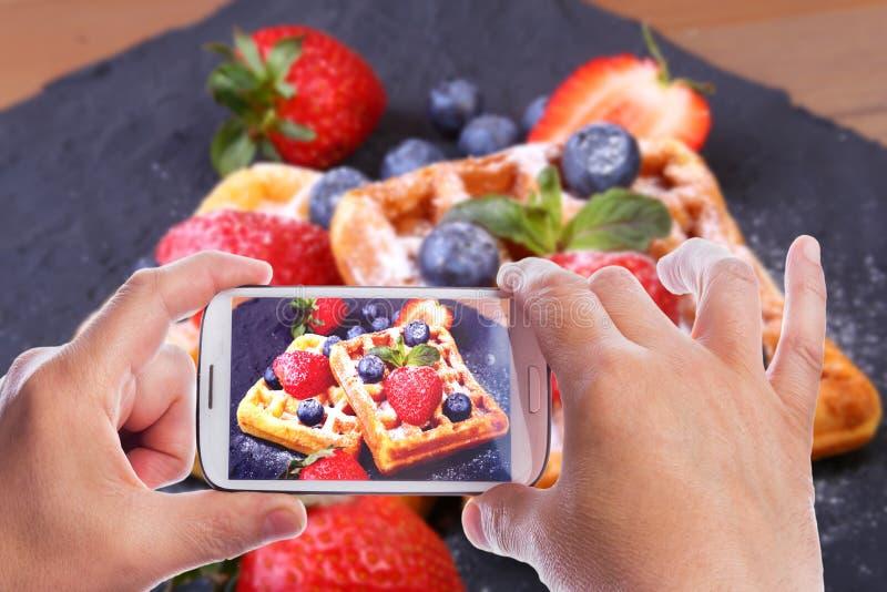 人的手用智能手机照相自创传统比利时华夫饼干用新鲜水果,莓果和搽粉 免版税库存图片