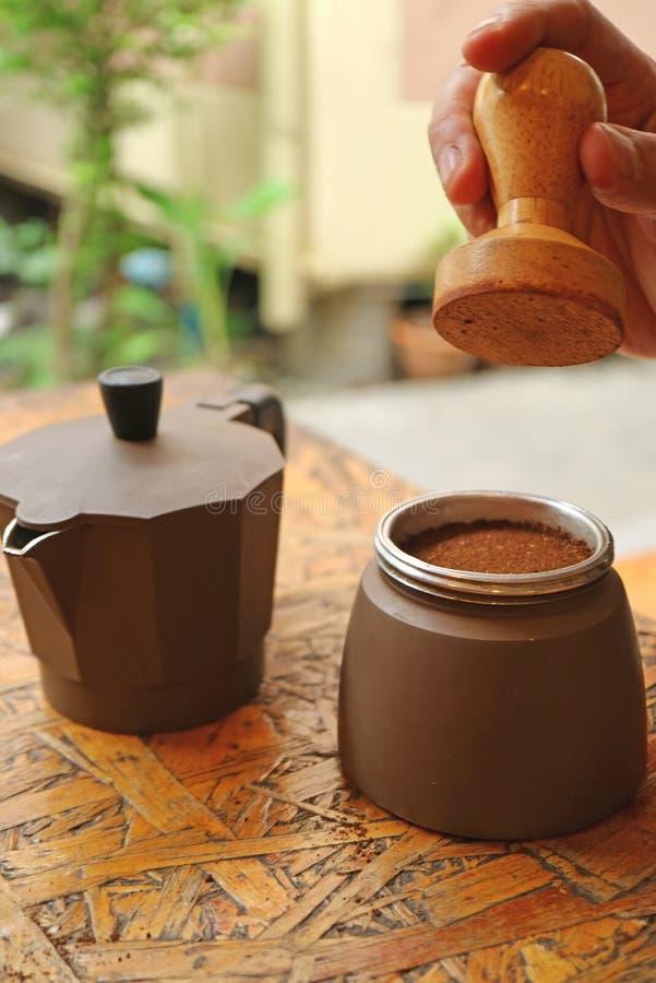 人的手轻拍一个平面的碾碎的咖啡的藏品堵塞器在酿造在罐前 图库摄影