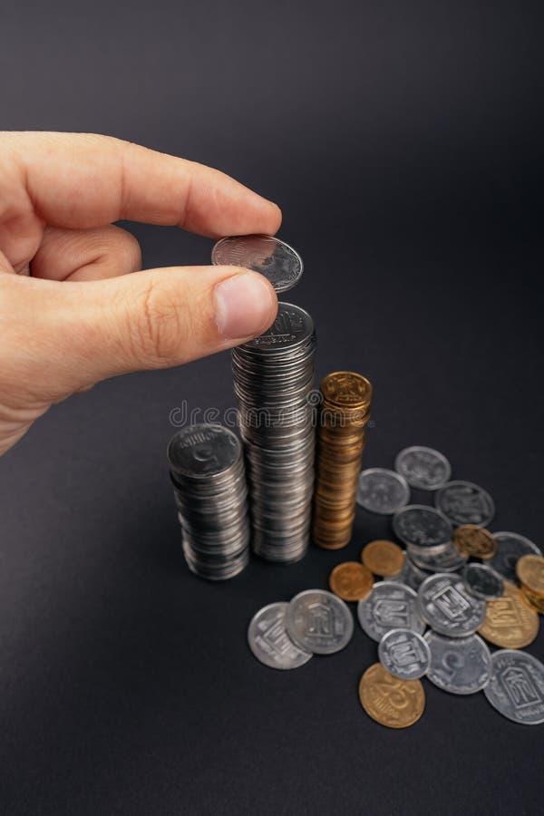 人的手预先设定的攒钱概念投入金钱硬币堆增长的事务在黑暗的背景乌克兰hryvnia 库存图片