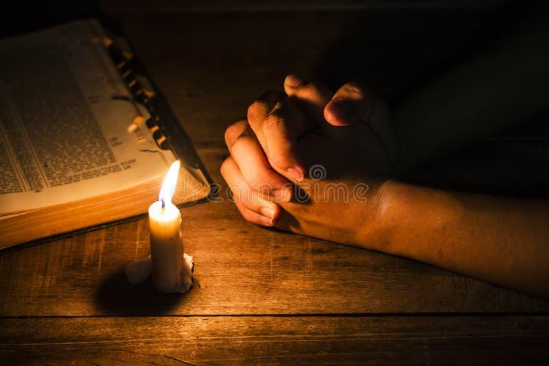 人的祈祷的手有蜡烛光的 免版税库存图片