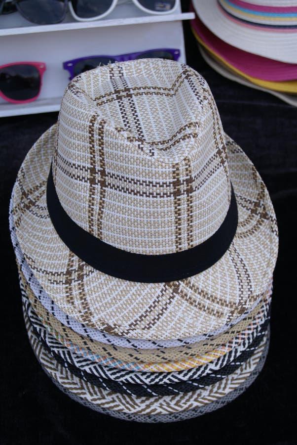 人的秸杆夏天帽子在一家商店在市场上 免版税库存图片