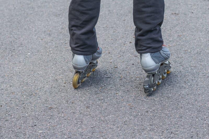 人的脚特写镜头有直排轮式溜冰鞋的在路 初学者,都市体育活动,在柏油路的路辗 复制 免版税图库摄影