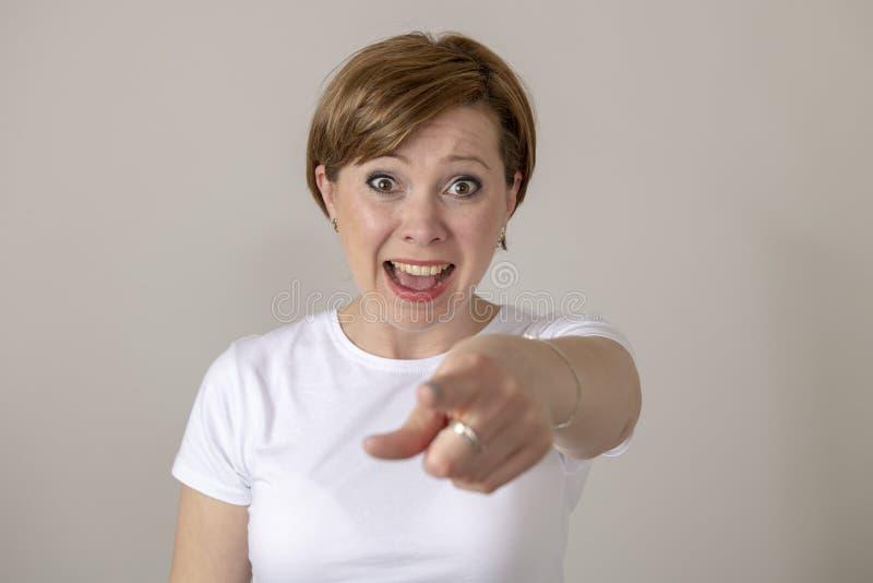 人的表示和情感 笑和指向照相机的年轻可爱的妇女 免版税库存图片