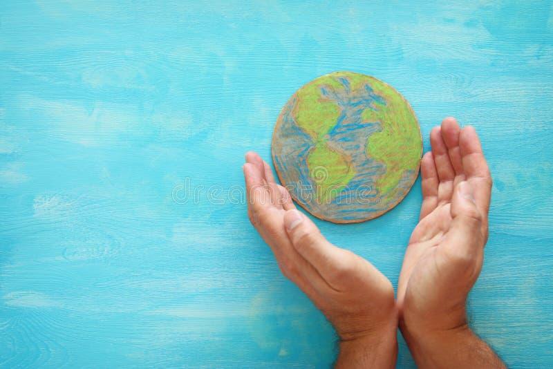 人的顶视图图象递拿着在蓝色木背景的地球地球 免版税库存图片