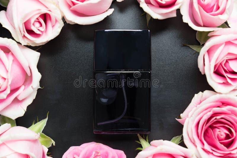 人的香水瓶与在黑色上升了 免版税库存照片