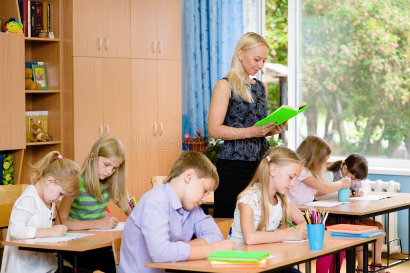 读他们年轻人的类的学生写任务 免版税图库摄影