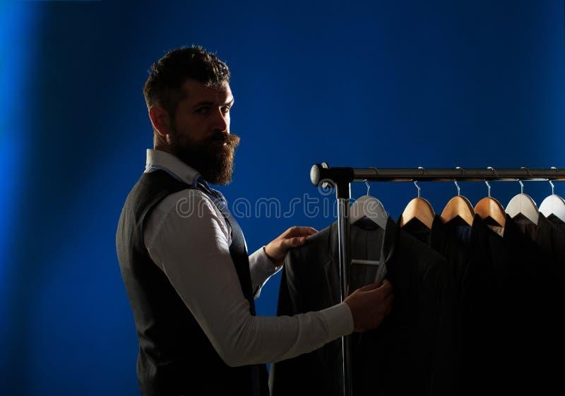 人的lothing,购物在精品店 裁缝,剪裁 人衣服,裁缝在他的车间 典雅的人的衣服垂悬 库存照片