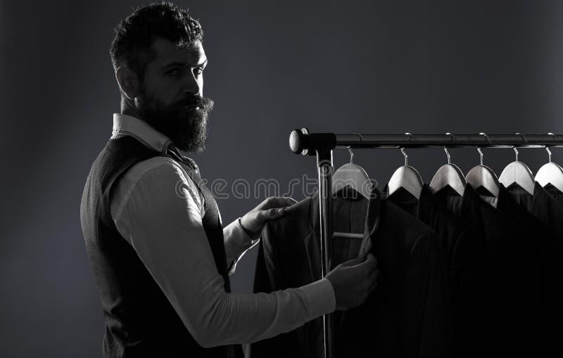 人的lothing,购物在精品店 裁缝,剪裁 人衣服,裁缝在他的车间 典雅的人的衣服垂悬 免版税库存图片