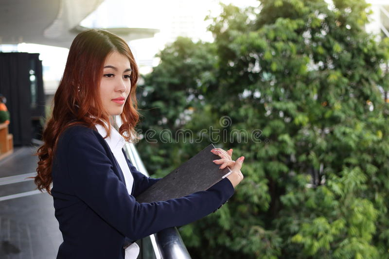年轻人相当亚裔女商人画象拿着剪贴板和很远注视着公开室外背景的 库存图片