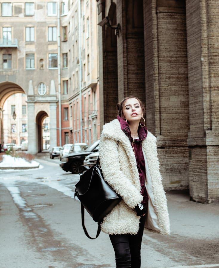 年轻人相当时髦的十几岁的女孩外面城市街道花梢时尚的穿戴了饮用奶震动 库存照片