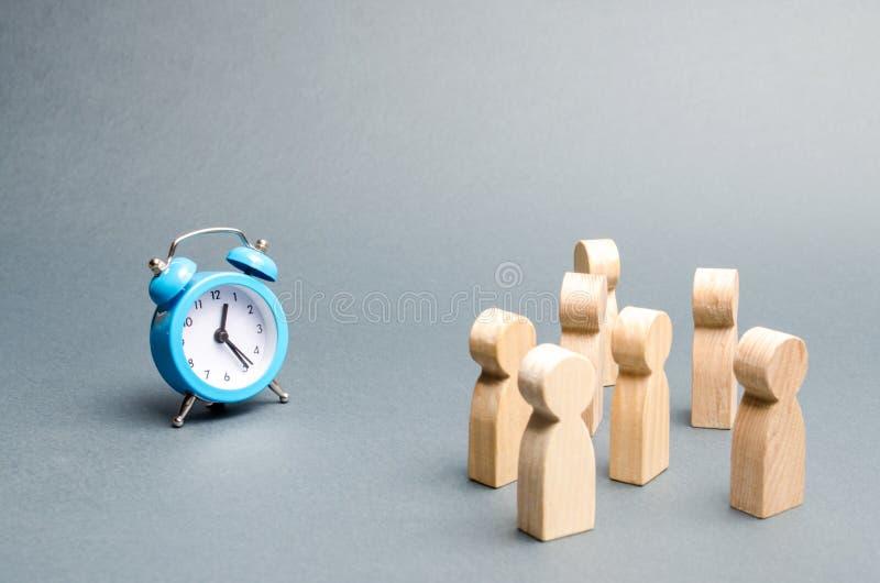 人看看人群时钟 注意人被束缚到时钟 等待的事件随着时间的推移 拆迁小时 库存照片