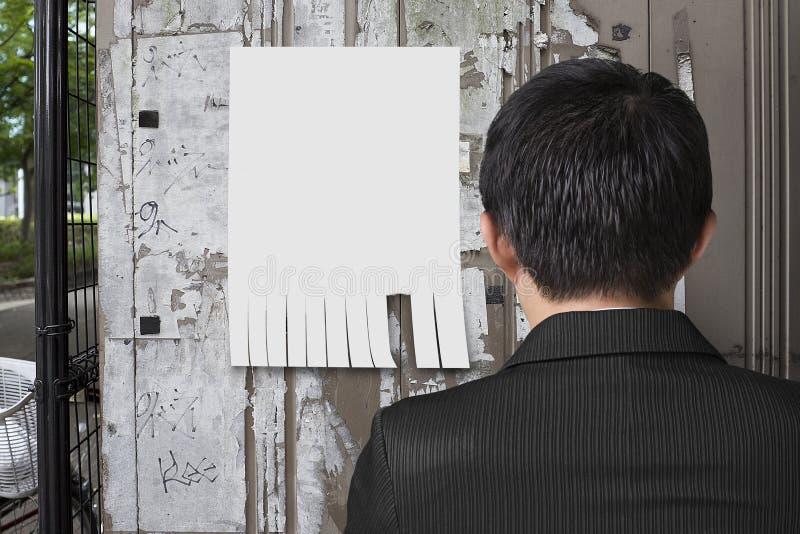 人看看在noticeboard的白皮书 免版税库存图片