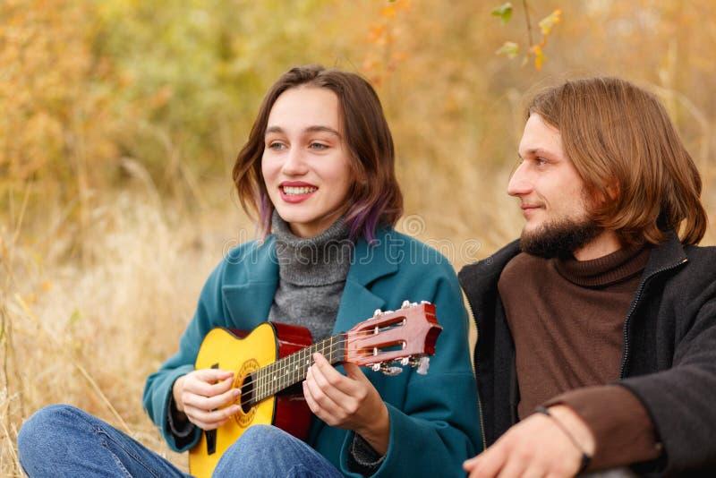 人看起来使用在秋天森林特写镜头的尤克里里琴的女孩 免版税图库摄影