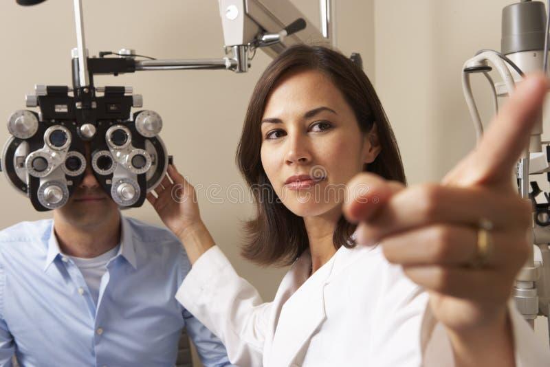 给人眼睛测试的手术的女性眼镜师 库存图片